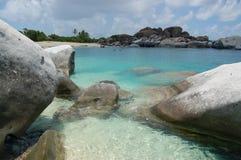 Pedregulhos, praia e águas do azure fotografia de stock