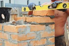 Pedreiro Bricklaying Concept Ferramentas da alvenaria Um pedreiro que usa um nível para verificar sua parede da construção da cas imagem de stock royalty free