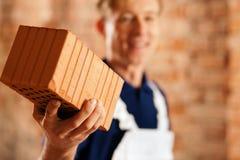 Pedreiro com o tijolo no canteiro de obras Imagens de Stock