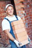 Pedreiro do pedreiro que leva tijolos vermelhos Fotografia de Stock