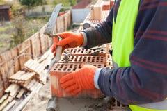 Pedreiro do trabalhador do pedreiro da construção que instala o tijolo vermelho Foto de Stock