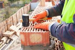 Pedreiro do trabalhador do pedreiro da construção que instala o tijolo vermelho com malho de borracha fora Imagens de Stock Royalty Free