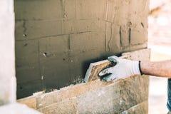 Pedreiro do trabalhador que coloca proximamente a telha de pedra na parede vertical Detalhes da indústria - canteiro de obras imagem de stock royalty free