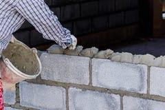 Pedreiro que coloca uma outra fileira de tijolos no local Imagens de Stock Royalty Free
