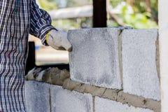 Pedreiro que coloca uma outra fileira de tijolos no local Foto de Stock