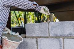 Pedreiro que coloca uma outra fileira de tijolos no local Fotografia de Stock