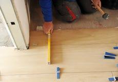 Pedreiro que verifica o nivelamento de um assoalho da faiança da porcelana com a ferramenta nivelada fotos de stock