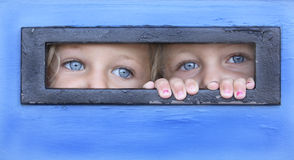 Peek a boo. Sisters hiding behind a door peeping thru a letter box Stock Images