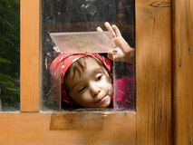 Peek-a-boo. Curious little girl in a cat's door Stock Image