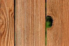 Peek-a-boo. Hole in a wooden fence Royalty Free Stock Photo