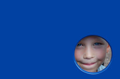 Peek a boo. Boy looking out through a round hole Royalty Free Stock Images