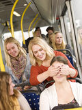 Peek a boo. Young women playing peek-a-boo on the bus royalty free stock photos