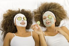 Peek-a-boo. Happy twins with anti-aging face masks. Cucumber slices covering theirs eyes. Ther're lying on towels Royalty Free Stock Images