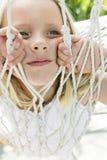 Peek-a-Boo. A cute girl peeking through a hammock net Royalty Free Stock Images
