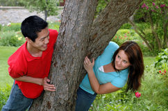 Peek a boo. Playful young couple in a garden Stock Photography