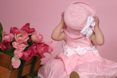 Peek a boo. Little girl hiding behind easter hat Stock Image