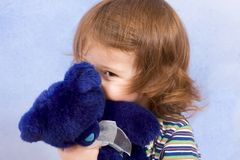 Peek-a-boo - child peeking from blue teddy bear. Peekaboo - shy kid holding blue Teddy bear and peeking from behind blue stuffed animal toy (blue background Royalty Free Stock Image