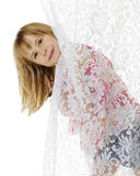 Peek-a-Boo Curtain. A cute elementary girl peeking her head out from behind a lace curtain.  On a white background Royalty Free Stock Photography