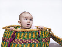 Peek-a-boo. Cute baby hiding in a basket Royalty Free Stock Photography