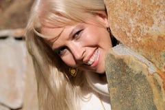 Peek A Boo Girl. Attractive blond girl peeking around stone wall Royalty Free Stock Photos