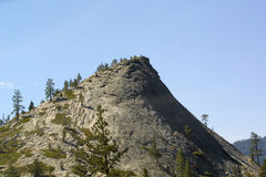 Peek over the hill. Granite hill top with pine trees and blue sky Royalty Free Stock Photography