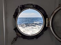 Peek through a porthole in an old ferry to see the waves of the ocean and the sky royalty free stock photography