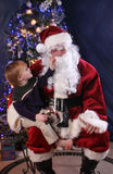 Peek at Santa. Little boy appearing to peek under santa's beard to see if its real stock photo