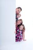 Peek sorridente della famiglia fuori Immagine Stock