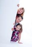 Peek sorridente della famiglia fuori Fotografie Stock Libere da Diritti
