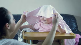 Peekaboo παιχνιδιού μητέρων με τη συνεδρίαση κοριτσιών μικρών παιδιών σε ένα highchair απόθεμα βίντεο