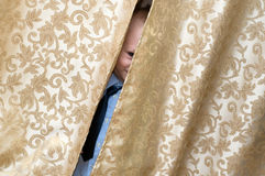 Peekaboo. Kid hiding behind a curtain Stock Image