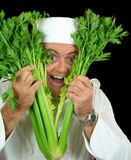 Peekaboo Chef. Pops his head through a bunch of fresh celery Royalty Free Stock Photography