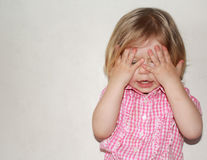 Peekaboo. Cute little girl playing hide and seek Royalty Free Stock Photo