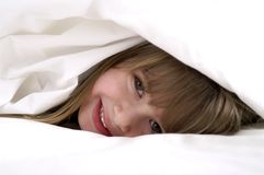 Peeking. A young girl playing in the sheets royalty free stock photo