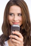 Peeking. Smiling young woman holding her cell phone looking at one site Royalty Free Stock Photography