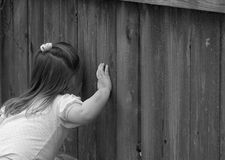 Peeking. Little girl peeking through wooden fence stock photography