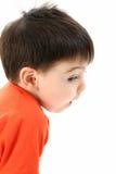 Peeking Around The Corner. Small boy peeking around to the side. Shot in studio over white stock image