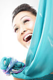 Peeking from behind silk. Asian model peeking from behind a silk curtain Royalty Free Stock Image