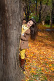 Peeking behind the tree in autumn. Royalty Free Stock Images