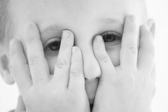 Peeking boy. A cute little caucasian boy hiding his face behind hands and peeking. Image in black and white stock image