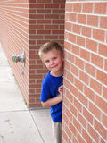 Peeking child. A young boy peeking around the corner of a brick wall Stock Image