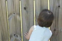 Peeking Through the Fence. Kid peeking through a backyard fence stock photos