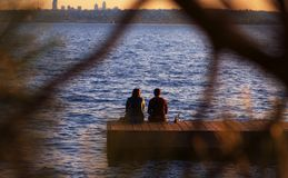 Peeking at Friends. A peek through a Pine Tree's branches at two friends who are sitting on a dock's edge taking in the evening's mood royalty free stock photo