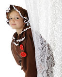 Peeking Gingerbread Girl. A cute elementary gingerbread girl peeking out from behind a lacey white curtain.  On a white background Royalty Free Stock Photos