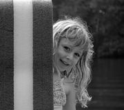 Peeking Girl in Black & White. Young girl peeking from behind a float at the lake stock images