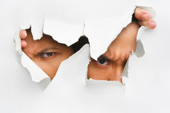 Peeking from hole in wall. Two people peeking from hole in wall showing their eyes only royalty free stock image