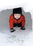 Peeking through Igloo Doorway. A bundled up two-year-old boy peers out of a homemade igloo Royalty Free Stock Image