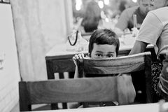 Peeking Kid in a candid moment. A candid photograph of a little kid peeking from his chair Stock Photo