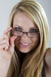 Peeking over her glasses. A pretty blond girl peeks over her eyeglasses and smiles into the camera Stock Photography