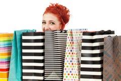 Peeking over her shopping bags Stock Photo